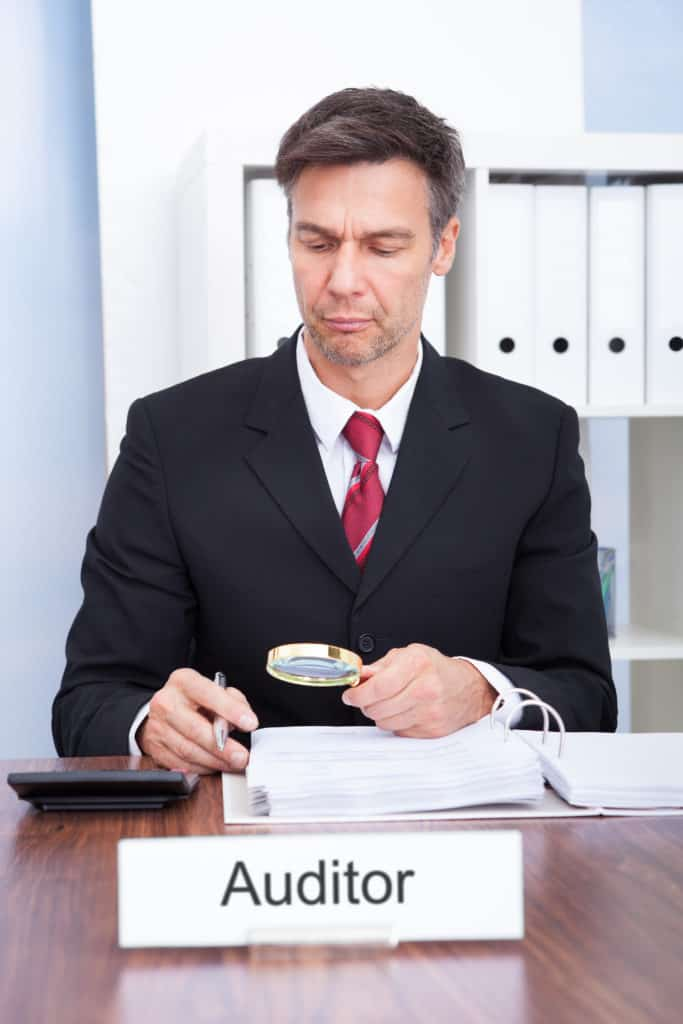Businessman Looking At Document Through Magnifying Glass